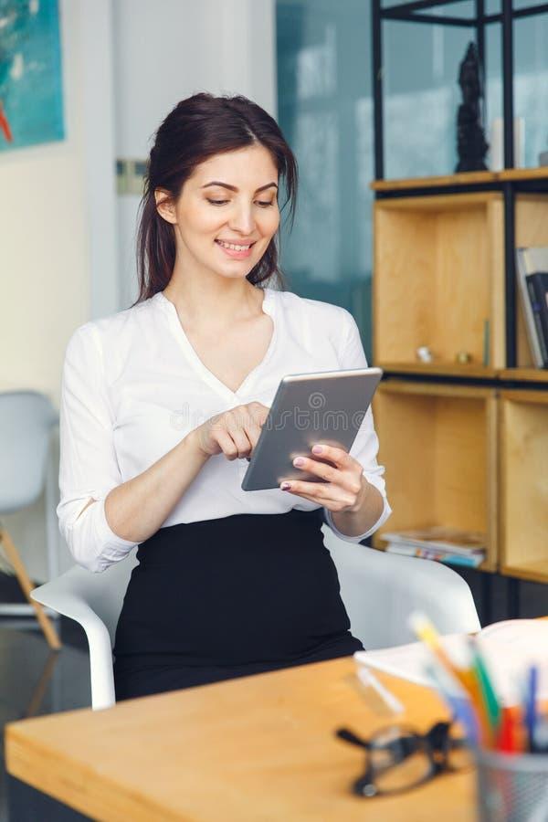 Mujer de negocios embarazada que trabaja en la tableta digital de la ojeada de la maternidad de la oficina que se sienta fotos de archivo libres de regalías