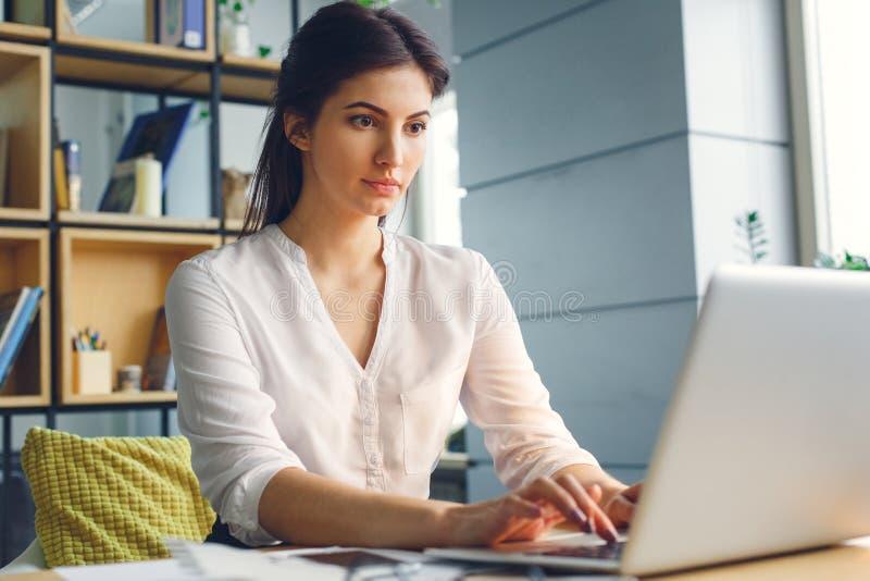Mujer de negocios embarazada que trabaja en mecanografiar que se sienta de la maternidad de la oficina en el ordenador portátil imagenes de archivo