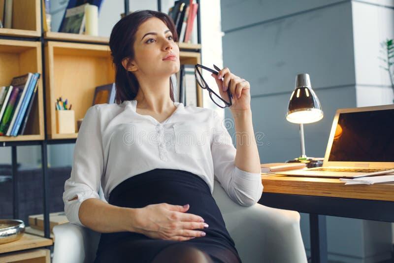 Mujer de negocios embarazada que trabaja en sentarse de la maternidad de la oficina pensativo foto de archivo