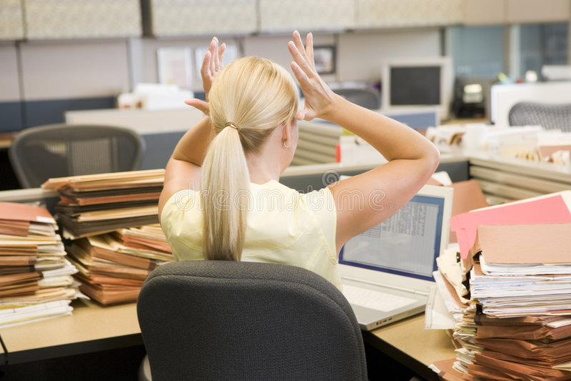 Mujer de negocios en el cubículo overworked y tensionado imagenes de archivo