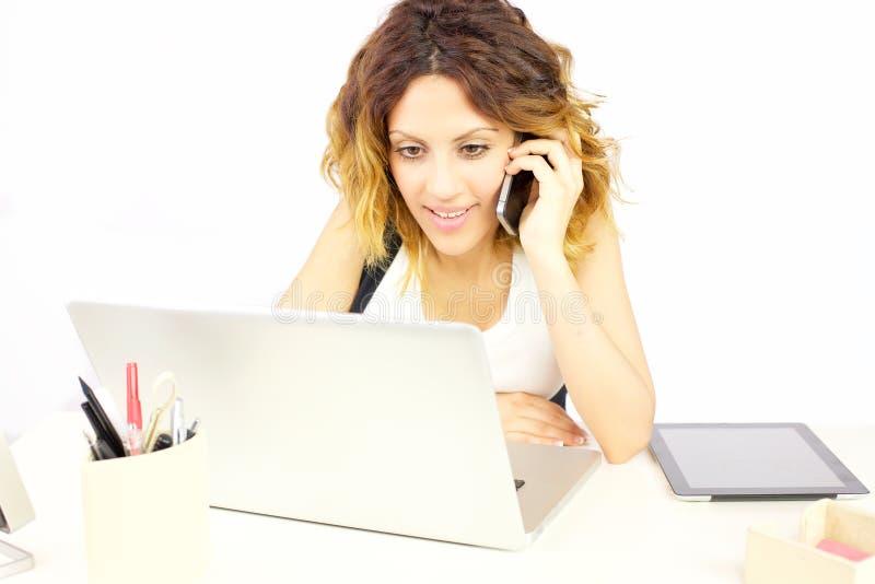 Mujer de negocios en el teléfono en PC de mirada feliz de la oficina fotos de archivo