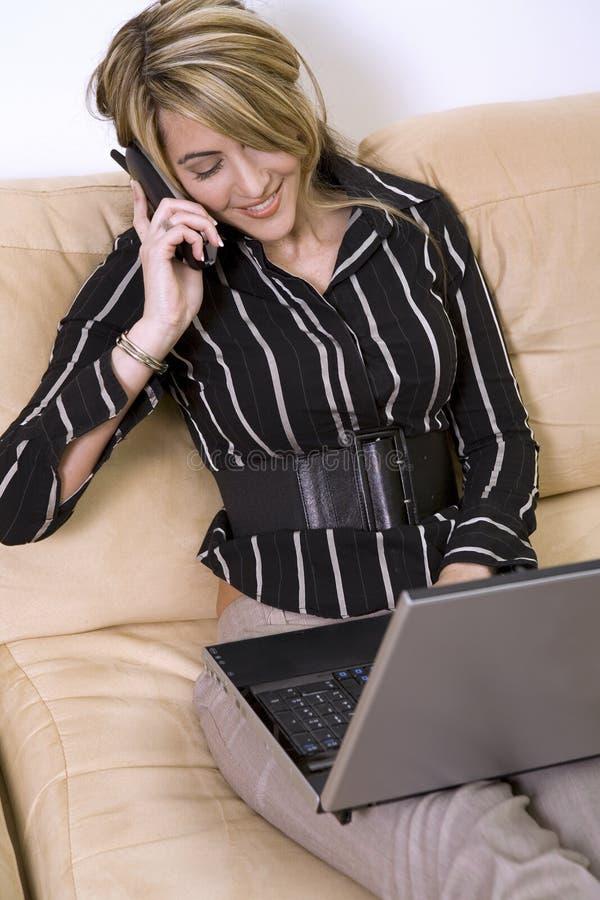 Mujer de negocios en el teléfono y la computadora portátil imagenes de archivo