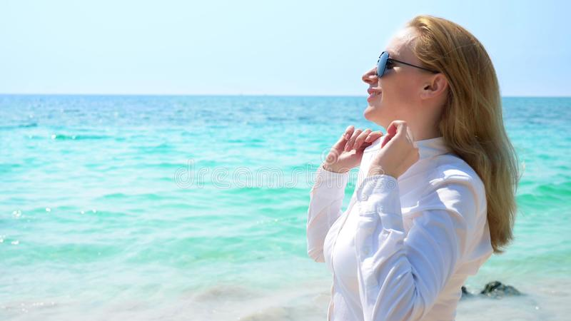 Mujer de negocios en gafas de sol en la playa Ella disfruta en el mar y el sol Ella desabrochó su camisa y respira adentro imagen de archivo
