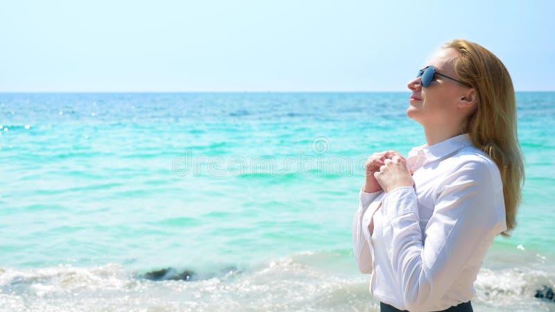 Mujer de negocios en gafas de sol en la playa Ella disfruta en el mar y el sol Ella desabrochó su camisa y respira adentro foto de archivo libre de regalías