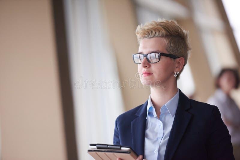 Mujer de negocios en la oficina con la tableta en frente como líder de equipo imagen de archivo