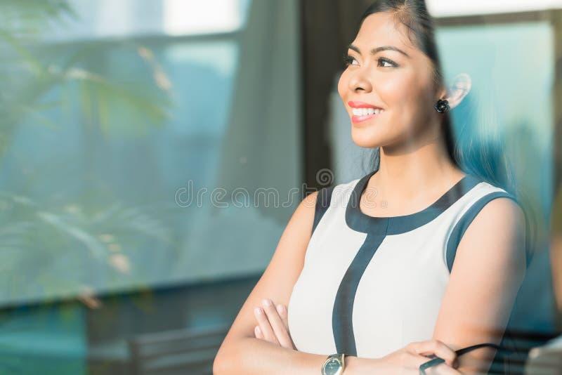 Mujer de negocios en la ventana de la oficina imagen de archivo