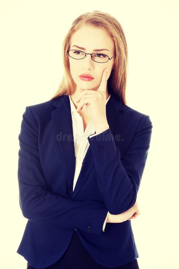 Mujer de negocios en lentes con el finger en mejilla fotografía de archivo