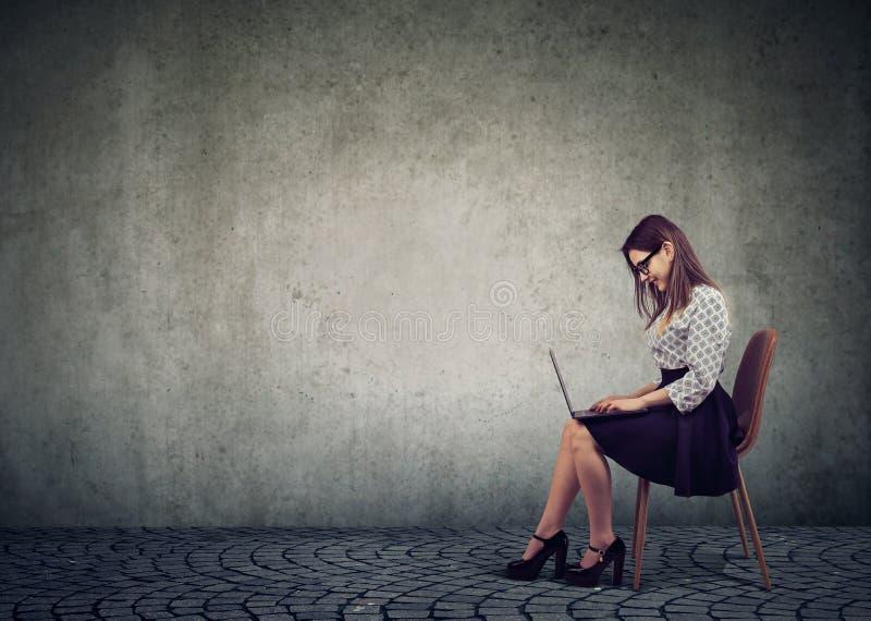 Mujer de negocios en los vidrios que se sientan en una silla y que usan el ordenador portátil imagen de archivo libre de regalías