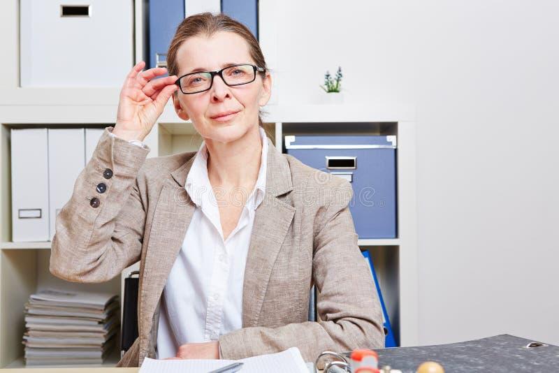 Mujer de negocios en oficina con los vidrios fotografía de archivo