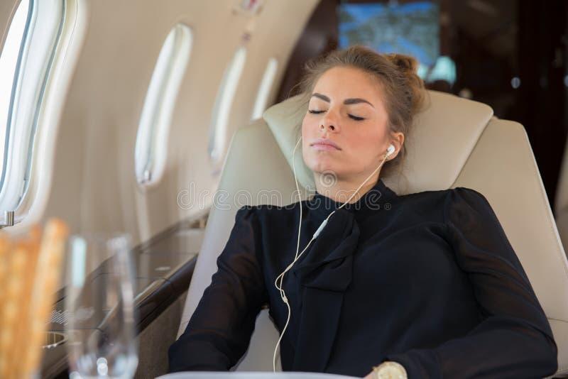 Mujer de negocios en un jet corporativo que se relaja y que escucha el musi imágenes de archivo libres de regalías