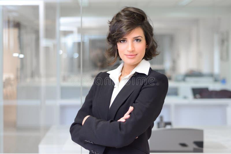 Mujer de negocios en una oficina. Brazos cruzados fotografía de archivo libre de regalías
