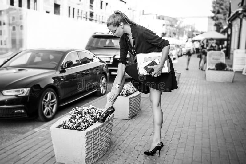 Mujer de negocios en vestido negro en la ciudad con los documentos imagenes de archivo