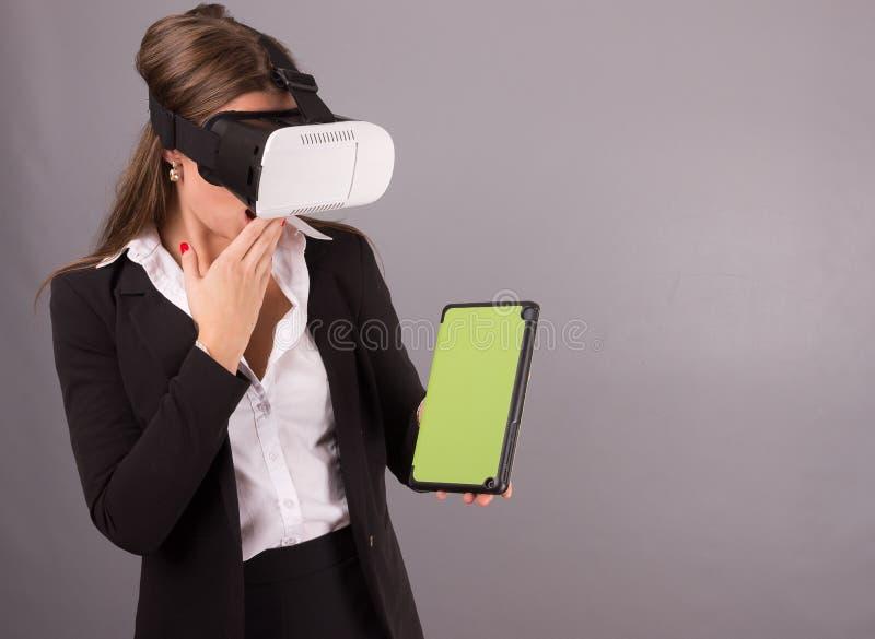 Mujer de negocios en vidrios usables de la tecnología VR Mujer joven confiada en un traje de negocios en auriculares de la realid foto de archivo