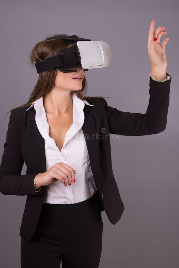 Mujer de negocios en vidrios usables de la tecnología VR Mujer joven confiada en un traje de negocios en auriculares de la realid fotografía de archivo