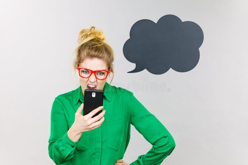 Mujer de negocios enojada que mira el teléfono, burbuja de pensamiento imagen de archivo libre de regalías
