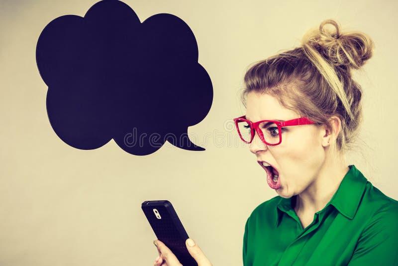 Mujer de negocios enojada que mira el teléfono, burbuja de pensamiento imagenes de archivo