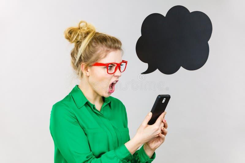 Mujer de negocios enojada que mira el teléfono, burbuja de pensamiento foto de archivo