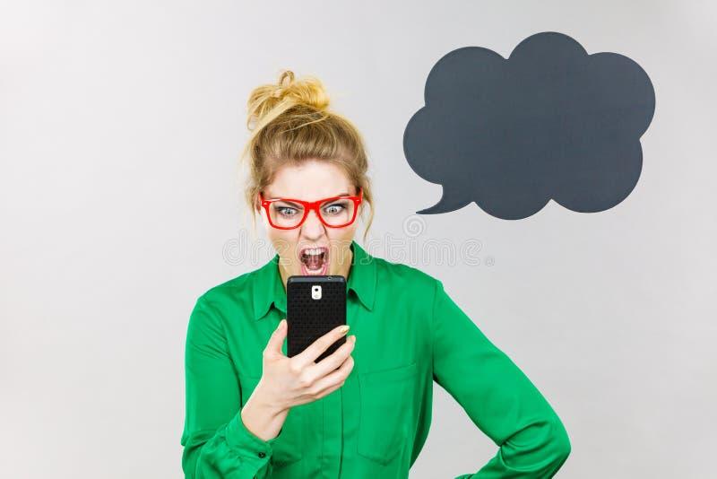 Mujer de negocios enojada que mira el tel?fono, burbuja de pensamiento imagen de archivo libre de regalías