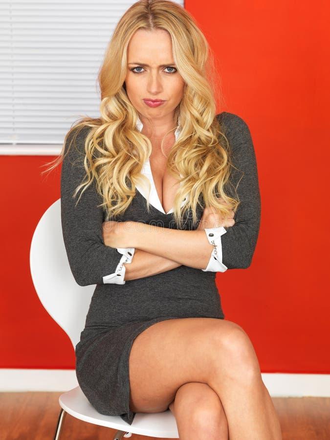 Mujer de negocios enojada que se sienta en una silla fotografía de archivo