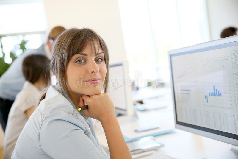 Mujer de negocios entre hombres de negocios en la oficina imagen de archivo