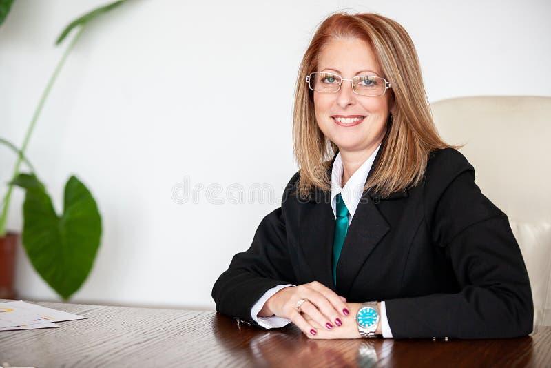 Mujer de negocios envejecida media en su oficina fotografía de archivo