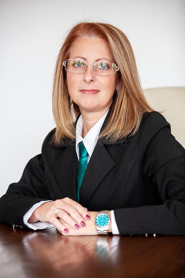 Mujer de negocios envejecida media en su oficina fotos de archivo
