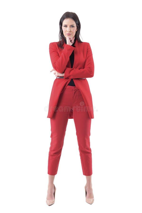 Mujer de negocios escéptica sospechosa escéptica que mira fijamente la cámara con la mano en la barbilla imagenes de archivo