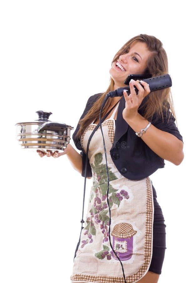Mujer de negocios experimentada que cocina y que habla en el teléfono fotos de archivo