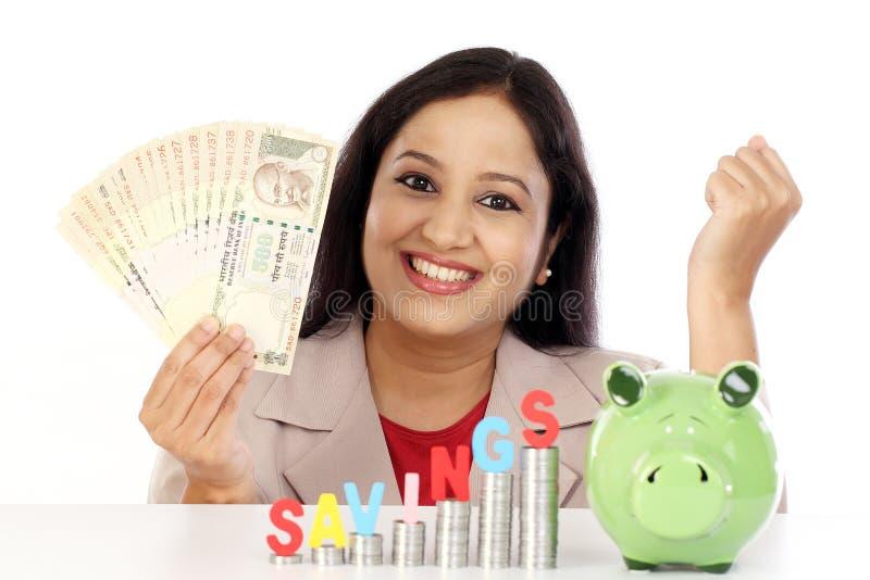 Mujer de negocios feliz con la pila de monedas imagen de archivo