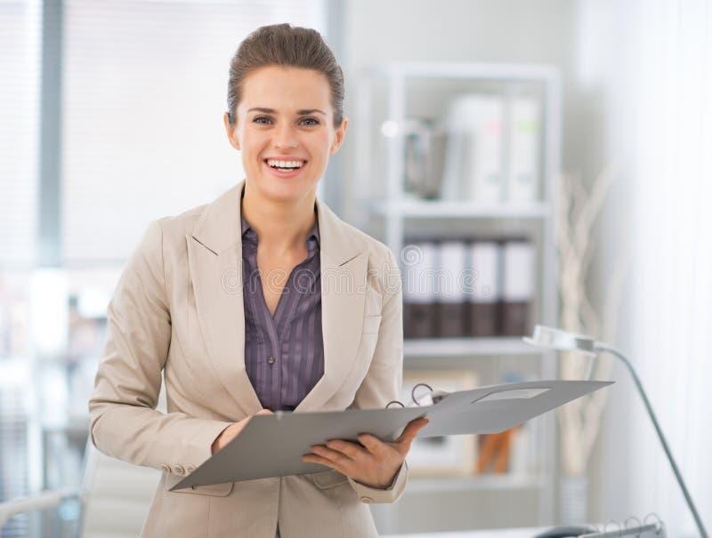 Mujer de negocios feliz con los documentos en oficina fotografía de archivo
