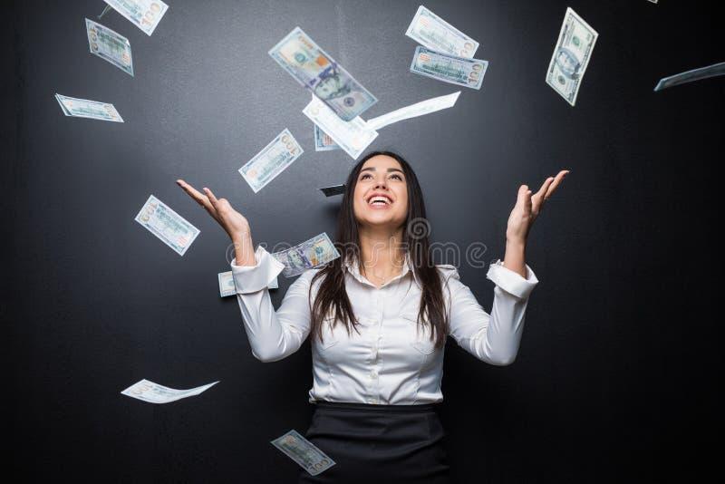 Mujer de negocios feliz debajo de una lluvia del dinero hecha de los dólares aislados en negro foto de archivo libre de regalías