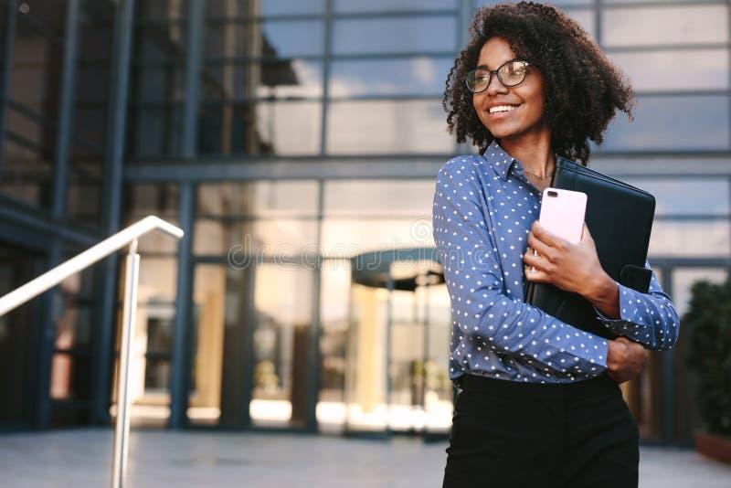 Mujer de negocios feliz derecha fuera de un edificio de oficinas fotos de archivo libres de regalías
