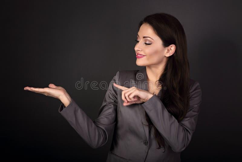 Mujer de negocios feliz en el traje gris que muestra y que señala el finge imagenes de archivo