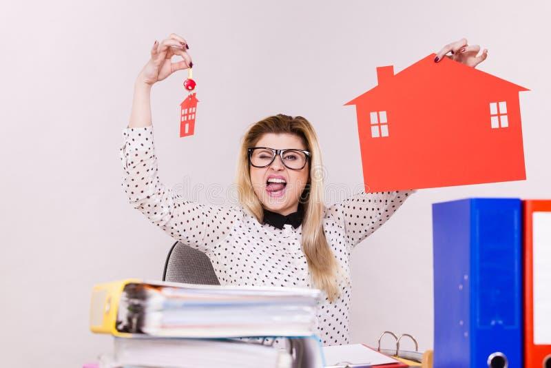 Mujer de negocios feliz en la oficina que sostiene la casa fotos de archivo