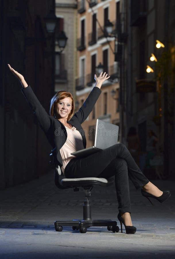 Mujer de negocios feliz joven que se sienta en silla de la oficina en la calle con el ordenador portátil fotografía de archivo libre de regalías