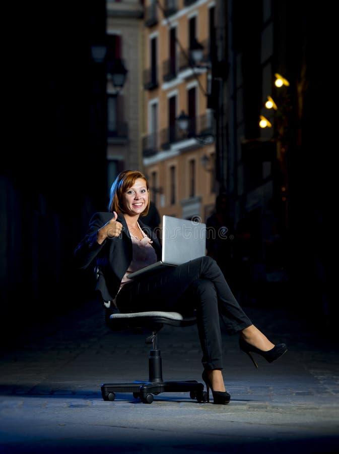Mujer de negocios feliz joven que se sienta en silla de la oficina en la calle con el ordenador portátil imagen de archivo