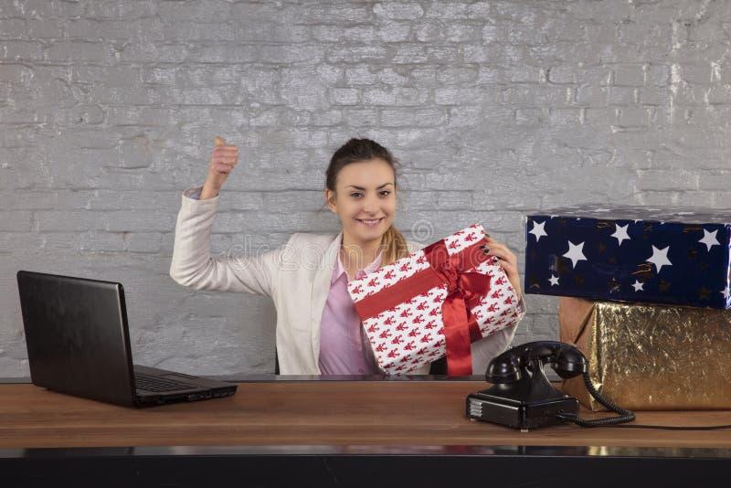 Mujer de negocios feliz, llevando a cabo un presente hermoso en sus manos foto de archivo libre de regalías