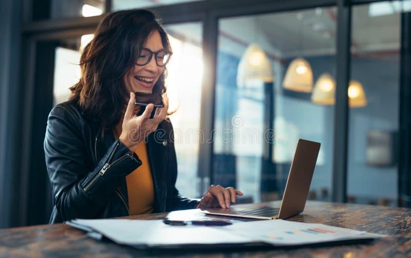 Mujer de negocios feliz que habla en el teléfono celular foto de archivo