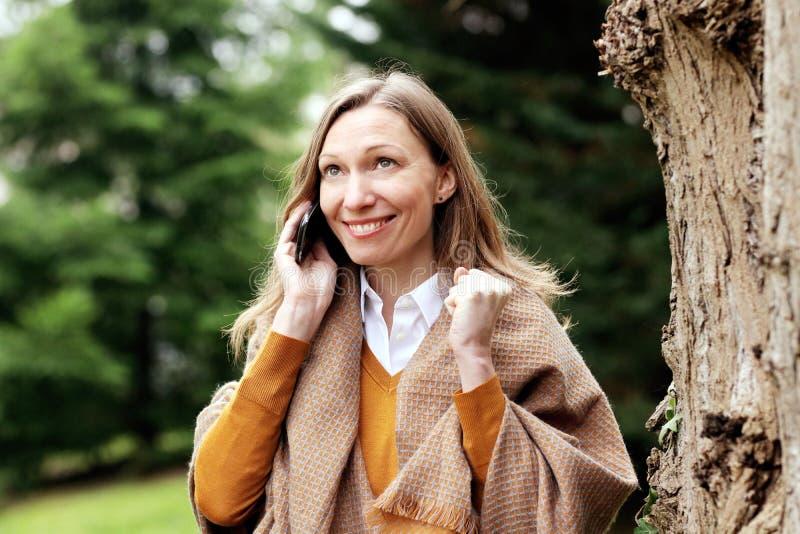 Mujer de negocios feliz que habla en smartphone fotos de archivo libres de regalías