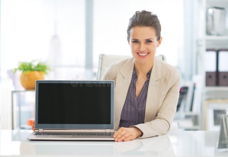 Mujer de negocios feliz que muestra a ordenador portátil la pantalla en blanco imagenes de archivo