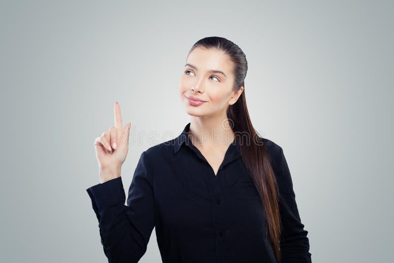 Mujer de negocios feliz que señala para arriba en fondo gris Retrato amistoso de la mujer foto de archivo