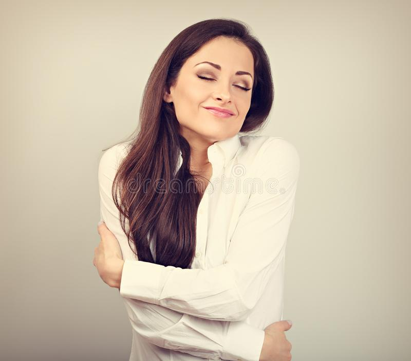 Mujer de negocios feliz que se abraza con la cara de goce emocional natural con los ojos cerrados en fondo del color Concepto del imagenes de archivo