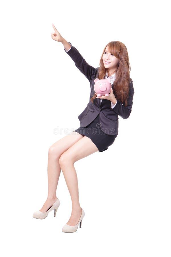 Mujer de negocios feliz que sostiene la hucha rosada imagen de archivo libre de regalías