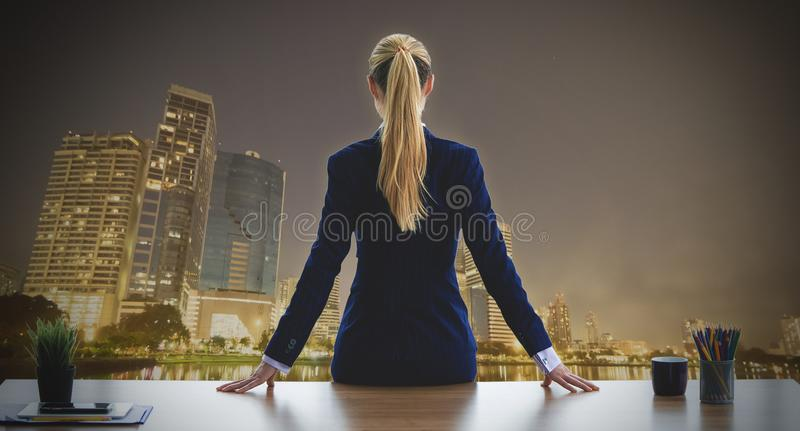 Mujer de negocios femenina que mira hacia fuera las ventanas de la noche de la ciudad para imagen de archivo