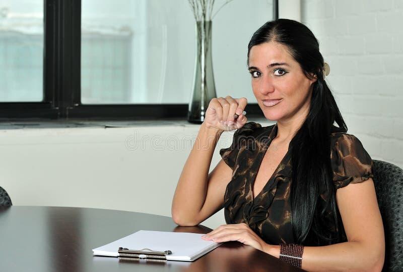 Mujer de negocios femenina triguena en la sala de reunión imagenes de archivo