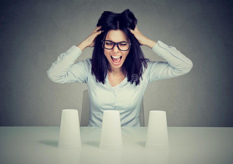 Mujer de negocios frustrada joven que juega un truco de conjuración incapaz de tomar una decisión fotografía de archivo libre de regalías
