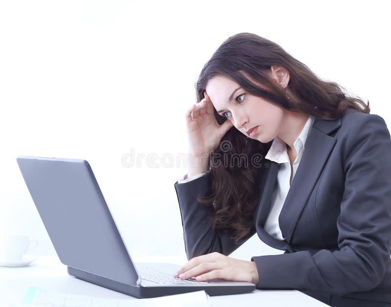 Mujer de negocios frustrada que se sienta delante de un ordenador portátil abierto fotos de archivo libres de regalías