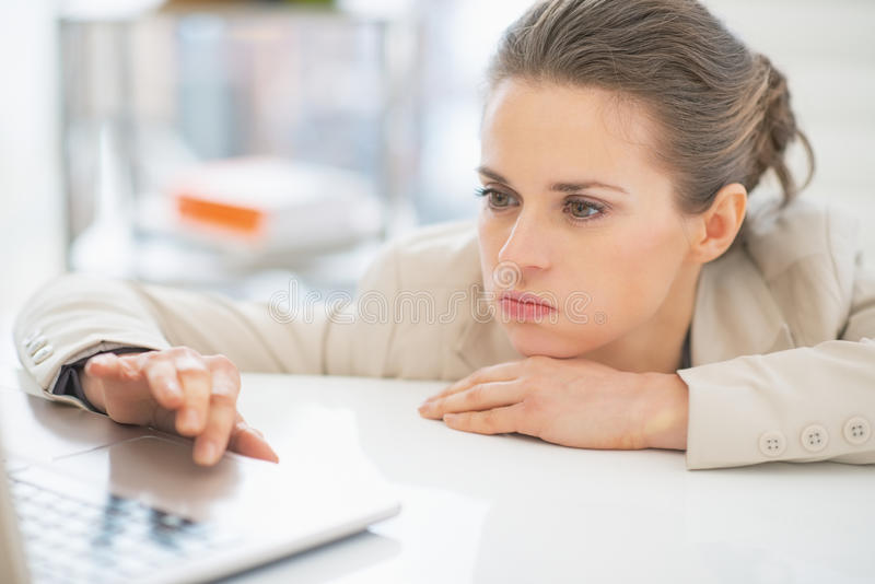 Mujer de negocios frustrada que trabaja con el ordenador portátil fotos de archivo
