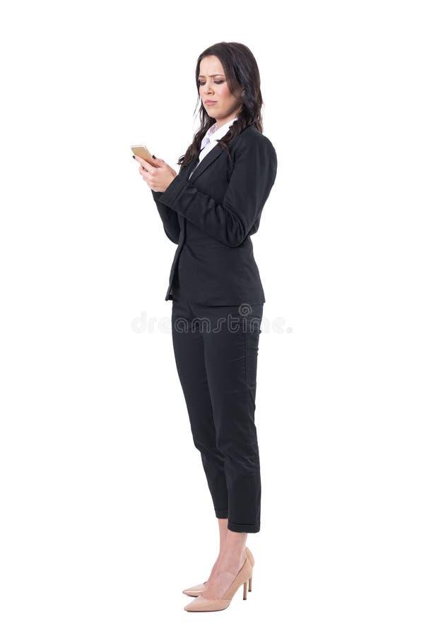 Mujer de negocios frustrada seria en traje negro usando el teléfono móvil foto de archivo libre de regalías