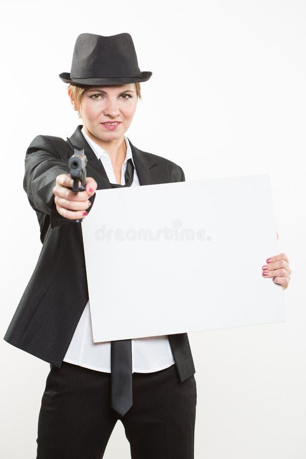 Mujer de negocios hermosa con el arma olding una cartelera en blanco imagenes de archivo